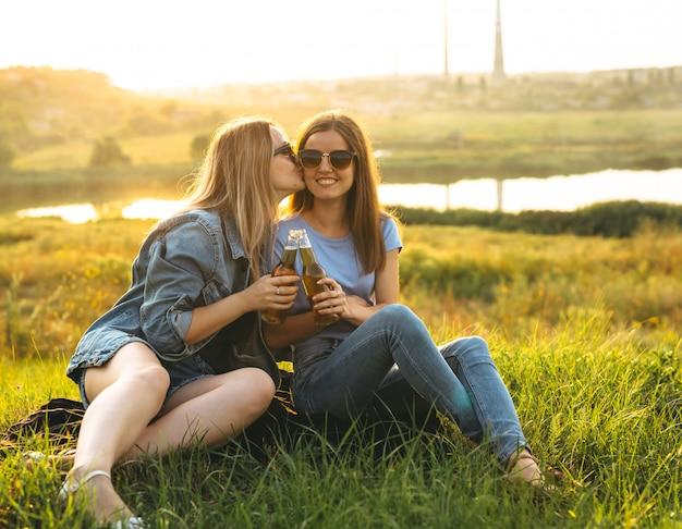 Duas meninas alegres e jovens amigos com óculos de sol, bebendo cerveja e aproveitando o tempo passado juntos ao pôr do sol.