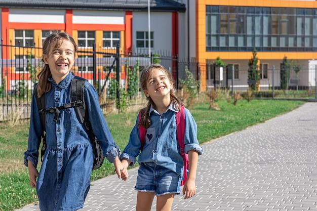 Duas meninas alegres vão para a escola de mãos dadas.