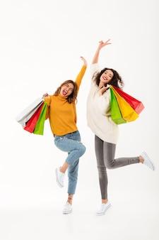 Duas meninas alegres verticais em blusas com pacotes se alegra sobre parede branca