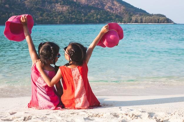 Duas meninas asiáticas bonitos da criança pequena que mantêm o chapéu que senta-se e que joga junto na praia