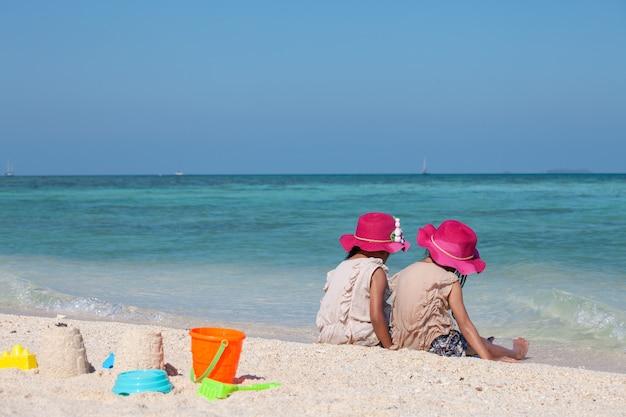 Duas meninas asiáticas bonitos da criança pequena que sentam e que jogam com areia junto na praia