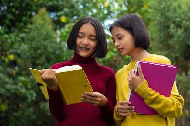 Duas meninas asiáticas conversando e segurando um caderno na natureza
