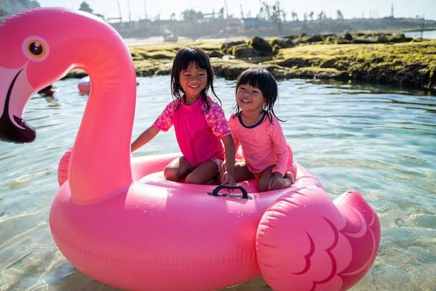 Duas meninas asiáticas felizes andando em uma bóia de flamingo