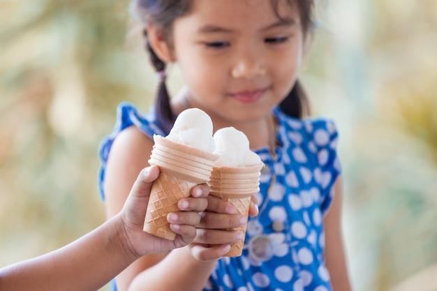 Duas meninas asiáticas segurando cone de waffle de sorvete de derretimento em tom de cor vintage