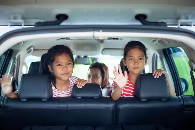 Duas meninas asiáticas sentadas no banco de trás de um carro, prontas para ir de férias com os pais
