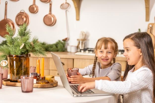 Duas meninas assistindo a escola online enquanto está sentado à mesa da mesa da sala de jantar.