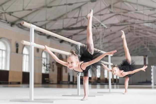 Duas meninas bailarina esticando as pernas para cima com suporte barre na aula de dança