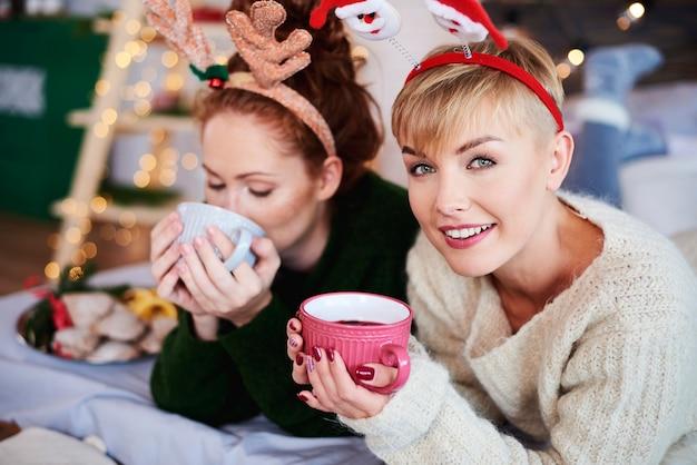 Duas meninas bebendo chá quente ou vinho quente
