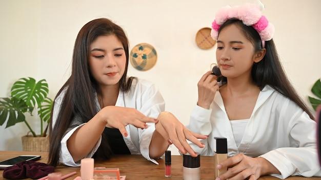 Duas meninas blogueiras de beleza apresentando produtos cosméticos de beleza para a rede social.