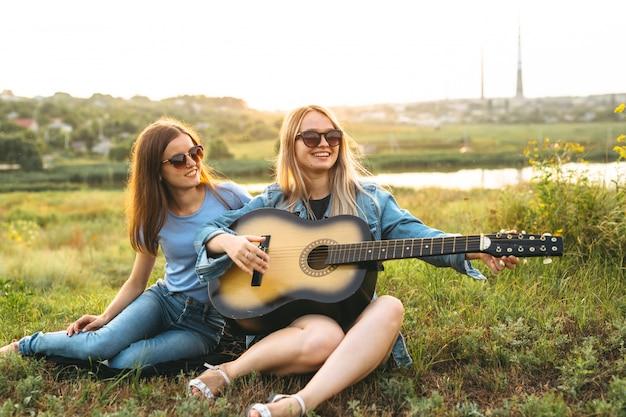 Duas meninas bonitas, aproveitando seu tempo juntos e tocando guitarra ao pôr do sol