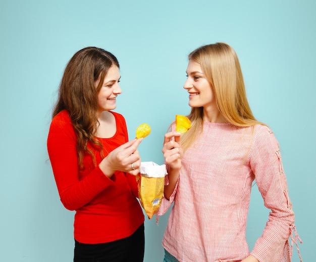 Duas meninas bonitas comendo batatas fritas e são alegres sobre um fundo azul