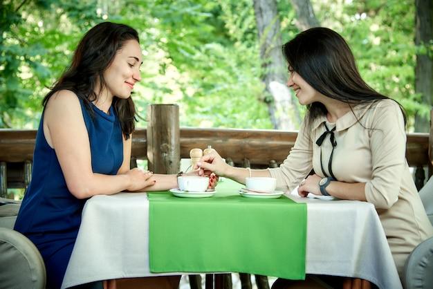 Duas meninas bonitas conversam em um café e bebem o café.