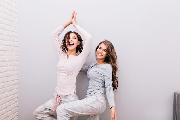 Duas meninas bonitas de pijama à noite, se divertindo na parede cinza. garota com cabelo encaracolado, tentando fazer ioga.