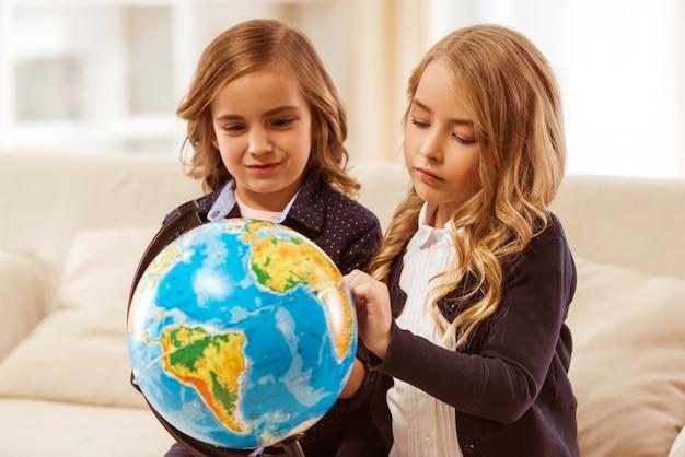 Duas meninas bonitas em revestimentos escuros consideram o globo.