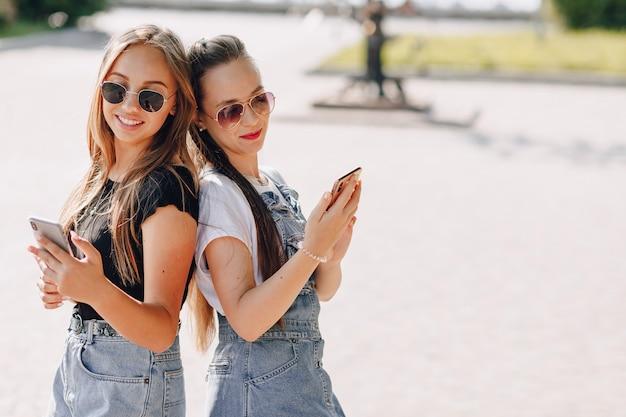 Duas meninas bonitas em uma caminhada no parque com telefones. dia ensolarado de verão, alegria e amizades.