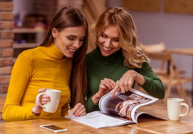 Duas meninas bonitas estão se comunicando, lendo revista.