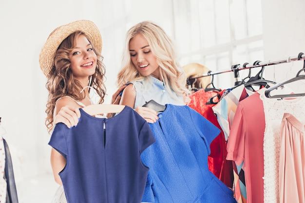 Duas meninas bonitas olhando vestidos e experimentá-lo enquanto escolhe na loja