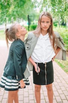Duas meninas bonitas posando na frente de sua escola. crianças adoráveis se sentindo muito animadas com a volta à escola