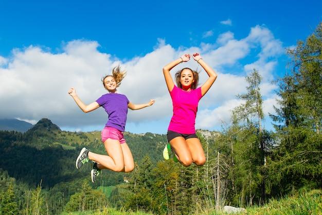 Duas meninas bonitas pulando na grama em um cenário de montanha