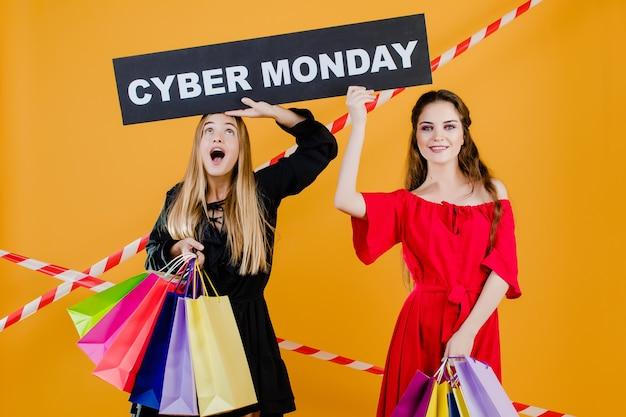 Duas meninas bonitas têm sinal de segunda-feira cyber com sacolas coloridas e fita de sinal isolado sobre amarelo