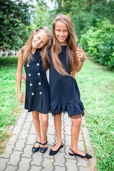 Duas meninas bonitinhas smilling posando na frente de sua escola.