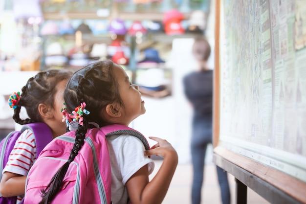 Duas meninas bonito criança asiática com mochila olhando mapa no quadro grande para viajar com diversão