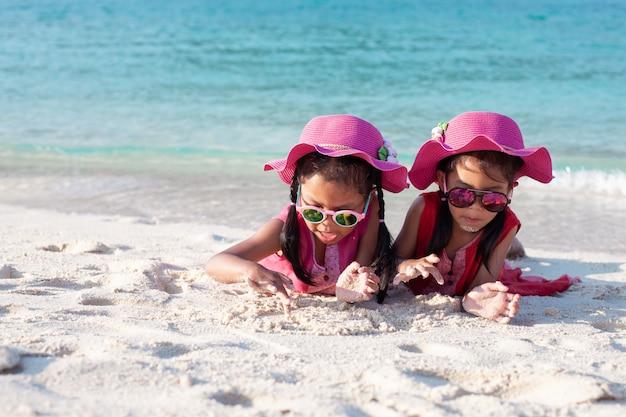 Duas meninas bonitos criança asiática usando chapéu-de-rosa e óculos de sol brincando com areia juntos na praia