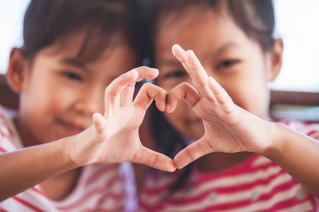 Duas meninas bonitos da criança asiática que fazem a forma do coração com mãos junto com o amor