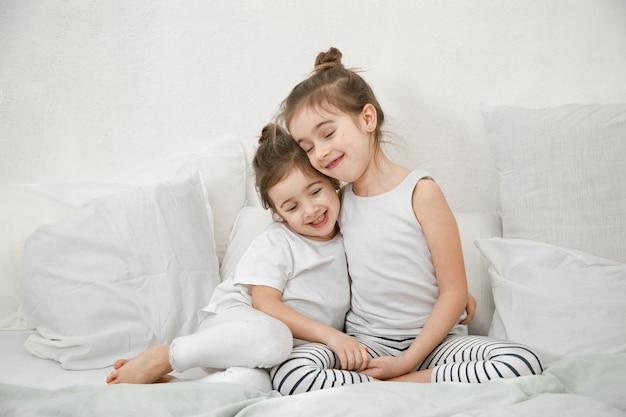 Duas meninas bonitos da irmã mais nova abraçam na cama no quarto.