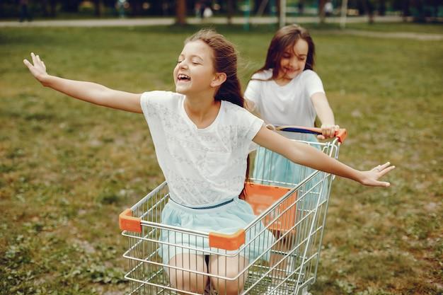 Duas meninas bonitos em camisetas brancas e saias azuis jogar no passeio de parque de verão