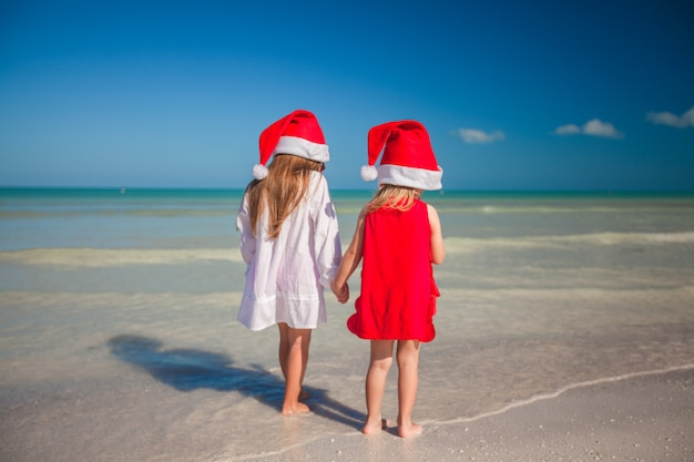 Duas meninas bonitos em chapéus de natal se divertem na praia exótica