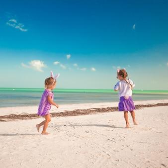 Duas meninas bonitos em orelhas de páscoa se divertem na praia exótica
