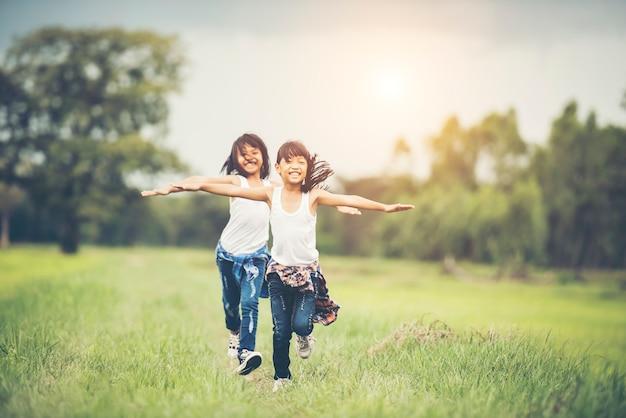 Duas meninas bonitos estão correndo na grama verde. melhores amigos.