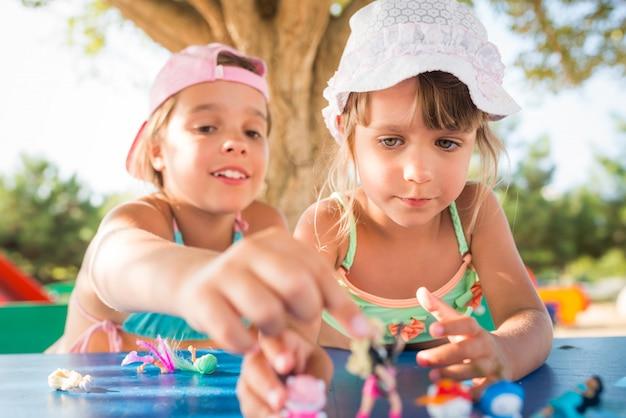 Duas meninas bonitos jogando bonecas ao ar livre
