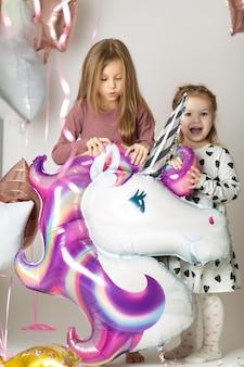 Duas meninas brincam com um grande balão unicórnio cercado por balões