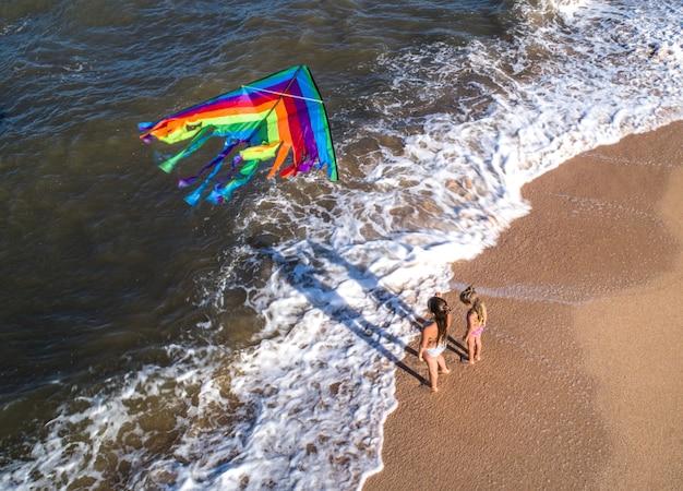 Duas meninas brincam com uma pipa à beira-mar