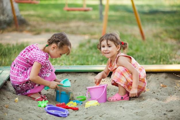 Duas meninas brincam na caixa de areia do parquinho