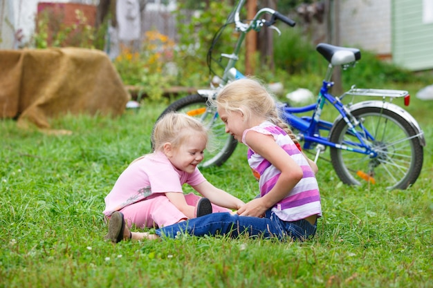 Duas meninas brincando na grama com a bola contra a bicicleta