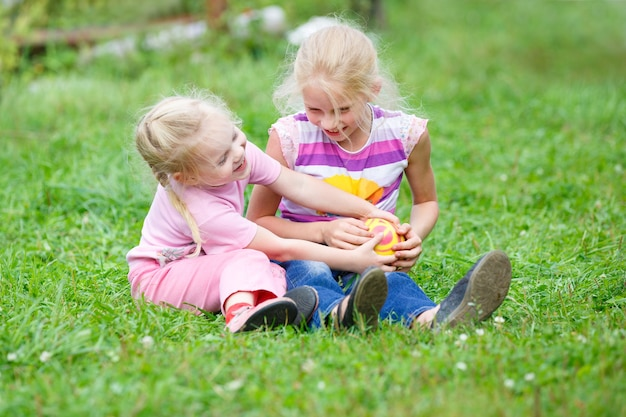 Duas meninas brincando na grama com a bola