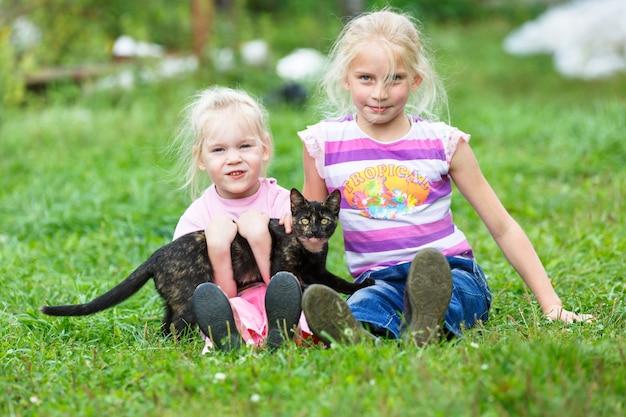 Duas meninas brincando na grama verde com um gato