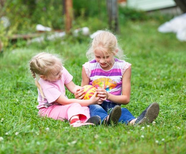 Duas meninas brincando na grama verde