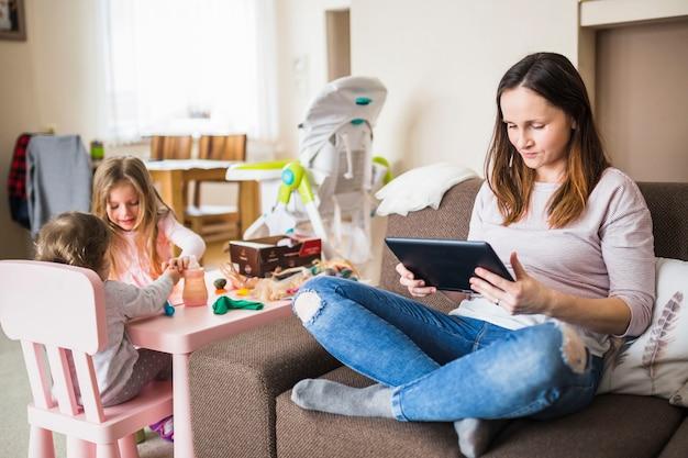 Duas meninas brincando perto de sua mãe usando tablet digital