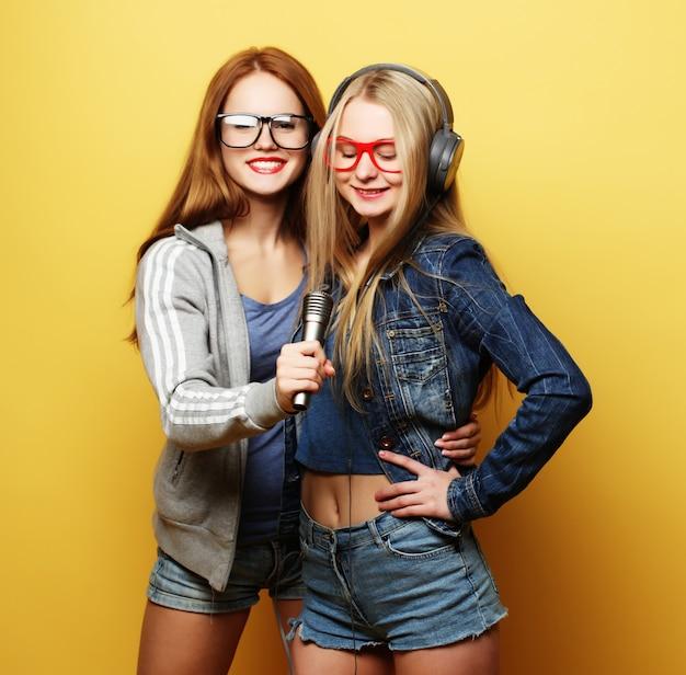 Duas meninas cantando sobre amarelo