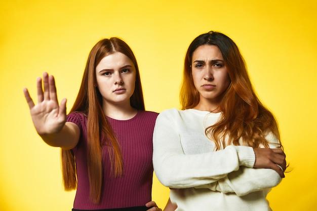 Duas meninas caucasianas ruivas sérias estão de pé ombro a ombro
