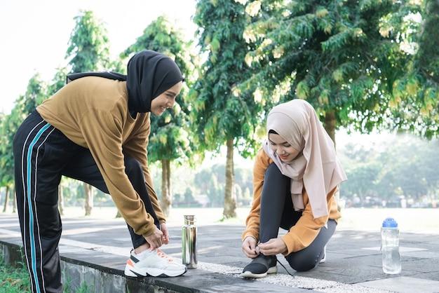 Duas meninas com capuzes ajustando os cadarços enquanto se arrumam antes de se exercitar no parque