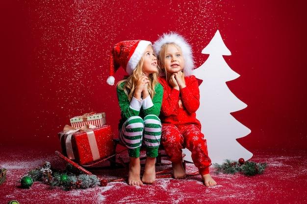 Duas meninas com chapéus de natal em um fundo vermelho sentadas perto de uma árvore de natal branca com presentes