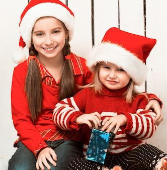Duas meninas com chapéus vermelhos sentadas no chão com presentes perto da árvore de ano novo