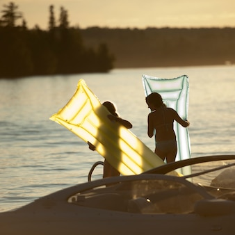 Duas meninas, com, flutuante, colchões, em, lago, de, a, madeiras, ontário