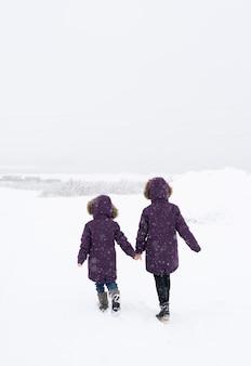 Duas meninas com jaquetas roxas idênticas caminhando juntas por um campo coberto de neve durante uma nevasca