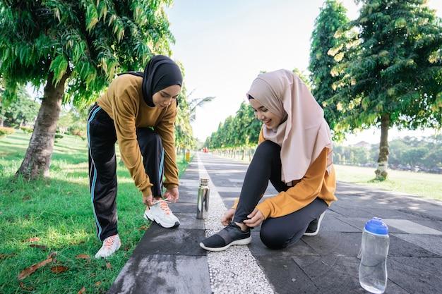 Duas meninas com lenços na cabeça carregando garrafas de bebida, agachadas no chão, conversando enquanto seguram e consertam cadarços após se exercitarem juntas à tarde